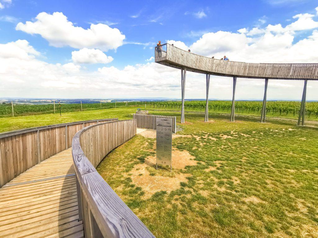 Vyhliadka má tvar kruhovej rampy – výseku 334° – a citlivo vystupuje nad krásne vinárske okolie.